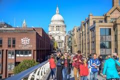 Туристы пересекая реку Темза путем идти через мост тысячелетия с собором St Paul в предпосылке, Лондоне, Великобритании стоковое изображение