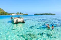 Туристы плавая и подавая акулы и хвостоколовые в красивом море на острове Moorae, Таити ПАПЕЭТЕ, ФРАНЦУЗСКОЙ ПОЛИНЕЗИИ Стоковое Изображение