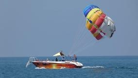 Туристы под яркой пестротканой посадкой парашюта на шлюпке видеоматериал