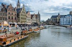 Туристы посещая исторический центр Gent при средневековые здания обозревая ` Graslei затаивают ` на реке Leie в городке Гента Стоковое Изображение