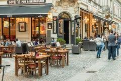 Туристы посещая и имея обед на внешнем центре города кафа ресторана в Бухаресте стоковое фото