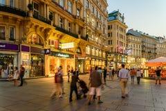 Туристы посещая и ходя по магазинам на улице Graben в ноче Стоковые Изображения