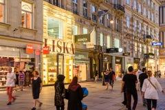 Туристы посещая и ходя по магазинам на улице Graben в ноче Стоковое Изображение