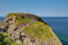 Туристы посещая мост веревочки Carrick-a-Rede в графстве антриме Северной Ирландии стоковые фотографии rf