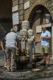 Туристы принимают воду к пластиковым бутылкам от выпивая фонтана на горячий летний день в Риме стоковая фотография