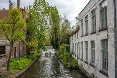 Туристы принимают езду шлюпки на канале в Брюгге, Бельгии, Европе стоковое изображение