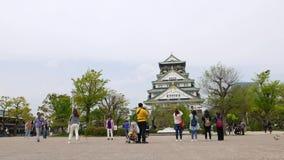 Туристы принимают фото против замка Осака, Японии акции видеоматериалы