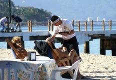 Туристы сервировки кельнера на пляже в Puerto Vallarta, Мексике стоковое фото rf