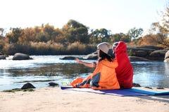 Туристы сидя в спальных мешках на диком пляже стоковое изображение rf