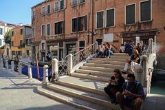 Туристы сидя на мосте в Венеции, Itlay стоковое фото rf