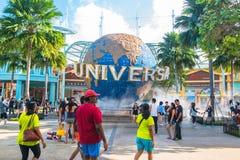 Туристы СИНГАПУРА - 13-ое января и посетители тематического парка фотографируя большой вращая фонтан глобуса перед универсалией Стоковое фото RF
