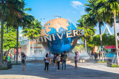 Туристы СИНГАПУРА - 13-ое января и посетители тематического парка фотографируя большой вращая фонтан глобуса перед универсалией Стоковые Фотографии RF