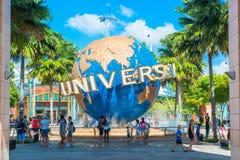 Туристы СИНГАПУРА - 13-ое января и посетители тематического парка фотографируя большой вращая фонтан глобуса перед универсалией Стоковая Фотография