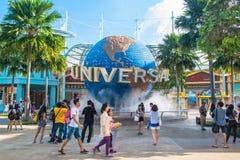 Туристы СИНГАПУРА - 13-ое января и посетители тематического парка фотографируя большой вращая фонтан глобуса перед универсалией Стоковое Изображение