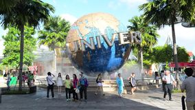 Туристы СИНГАПУРА - 13-ое января и посетители тематического парка фотографируя большой вращая фонтан глобуса перед универсалией акции видеоматериалы