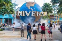 Туристы СИНГАПУРА - 13-ое января и посетители тематического парка фотографируя большой вращая фонтан глобуса перед универсалией Стоковые Изображения