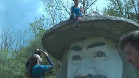 Туристы сфотографированы на памятнике к большой голове в шляпе Маленькая девочка в шлеме сидит на шляпе ` s памятника A сток-видео
