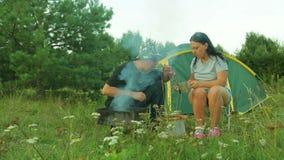 Туристы человека и женщины сидят рядом с куря барбекю, едят и выпивают чай видеоматериал