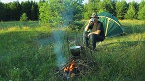 Туристы человека сидят на шатре, выпивая чай видеоматериал