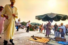 Туристы entertein чаровников и музыкантов змеек в рыночном мести Djemaa el Fna marrakesh Марокко стоковое фото rf