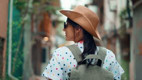 Турист активного backpacker женский идя на узкое touristic steadicam улицы города устанавливает съемку акции видеоматериалы