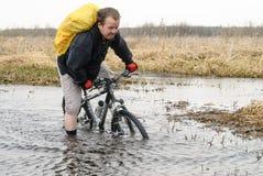 Турист велосипеда идет вдоль затопленной дороги Стоковые Изображения RF