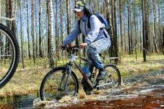 Турист велосипеда идет вдоль затопленной дороги Стоковая Фотография RF