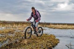 Турист велосипеда идет вдоль затопленной дороги Стоковые Фото