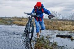 Турист велосипеда идет вдоль затопленной дороги Стоковое Изображение RF
