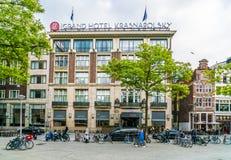 Турист входя в гостиницу Krasnapolsky 5 звезд грандиозную расположенное на квадрате запруды в центр Амстердама стоковые изображения