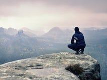 Турист в черноте сидит на cliff& x27; край s смотря к туманной холмистой долине стоковая фотография