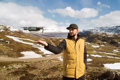 Турист Гая запускает quadrocopter с руками в горах стоковое изображение