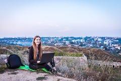 Турист девушки в природе при компьтер-книжка отдыхая от тщеты города стоковая фотография
