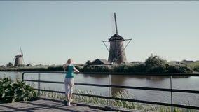 Турист девушки смотрит старые ветрянки в Нидерланд акции видеоматериалы
