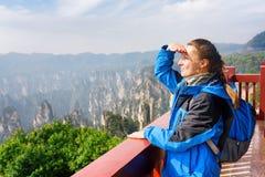 Турист детенышей усмехаясь женский наслаждаясь изумительным горным видом стоковое фото