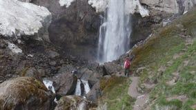Турист девушки идет к водопаду сток-видео