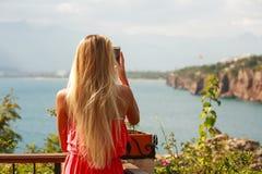 Турист девушки при smartphone фотографируя seashore Стоковые Фото