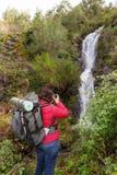 Турист девушки фотографируя водопад В Португалии, деревня Monchique Стоковая Фотография