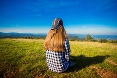 Турист женщины в крышке na górze холма наслаждаясь взглядом гор стоковая фотография