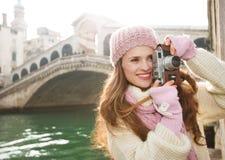 Турист женщины принимая фото с ретро камерой фото в Венеции Стоковая Фотография