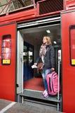 Турист женщины при чемодан приходя из поезда на станции Стоковое Изображение RF