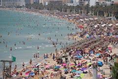 Турист загорает или ванна на море в толпить пляже El Arenal в Мальорке Стоковые Изображения
