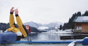 Турист зимнего дня приехал к его месту назначения изумляя большого озера и снежных леса и горы он принимая сток-видео