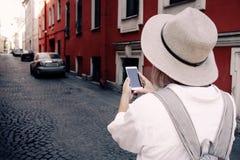 Турист используя навигацию app на мобильном телефоне перемещение карты dublin принципиальной схемы города автомобиля малое Стоковое фото RF