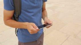 Турист ища необходимое место на gps составляет карту навигация на его smartphone видеоматериал