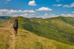 Турист идя вдоль следа в горах Стоковые Фотографии RF