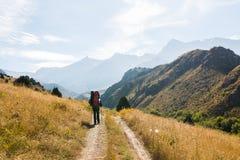Турист идя на дорогу к горам южного Тянь-Шань Казахстана Стоковое Изображение