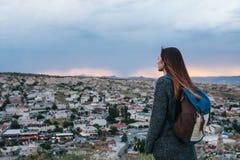 Турист молодой женщины от высокой точки смотря заход солнца над городком и мечтать Туризм, остатки, каникулы Стоковая Фотография