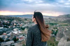 Турист молодой женщины от высокой точки смотря заход солнца над городом Goreme в Cappadocia в Турции и мечтать Стоковое Изображение RF