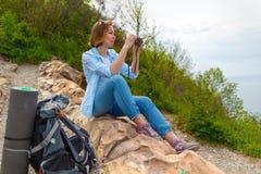 Турист молодой женщины путешествует через горы Женщина сидя на утесах и взятиях фото на камере стоковое изображение rf